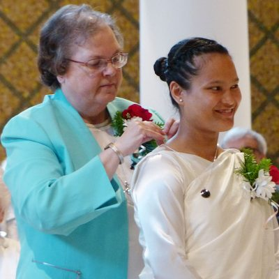Sister M. Veronique (Wiedower), CSC, gives Sister Metiful Mary Kharbani, CSC, the Holy Cross symbol as a sign of her commitment to living the vowed life in the Congregation of the Sisters of the Holy Cross.