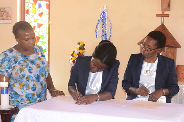 Sister Martha Nambi, CSC, signs her perpetual vows