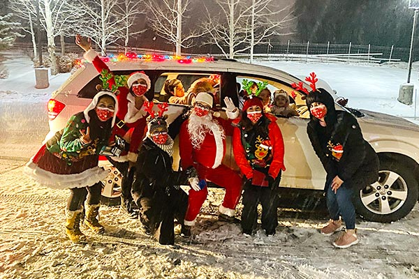 """Toes might have been cold, but hearts were warm as """"Santa"""" and her crew share drive-by holiday cheers with families in the Parents as Teachers program."""
