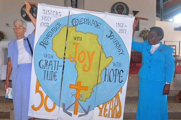 Sisters present a banner made to celebrate 50 years in Uganda