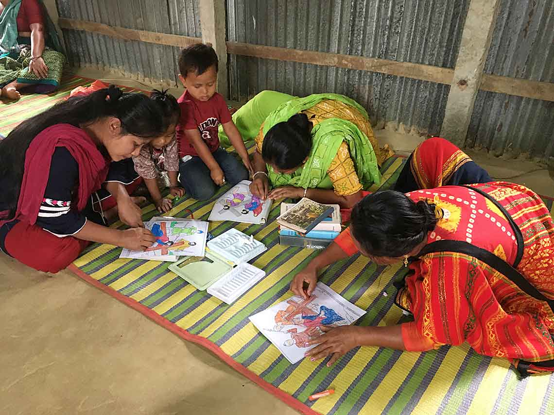 As they color pages depicting the Way of the Cross, women from the villages learn more about their Catholic faith.