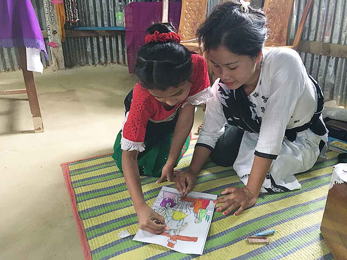 A student helps a young girl color a page depicting the Way of the Cross.