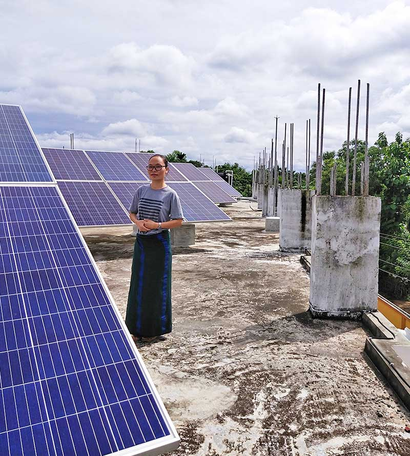 Sister Khochem Mossang, CSC, stands among the solar panels that are keeping the power flowing at Our Lady of Holy Cross School in Barakathal, India.