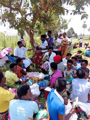 Mothers sit and wait under a tree to have their babies weighed by Sister Jacinta Mueni Munyao, CSC, during an immunization outreach program.