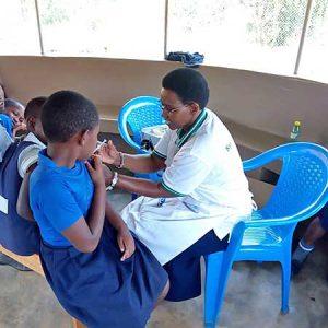 A ten-year-old school girls receive a human papillomavirus (HPV) vaccine injection from Sister Jacinta Mueni Munyao, CSC.
