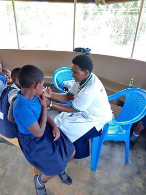 A ten-year-old school girls receive a human papillomavirus (HPV) vaccine injection from Sister Jacinta Mueni Munyao, CSC.