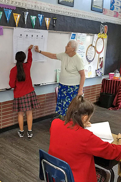 Holy Cross sisters living in Los Angeles, California, are addressing domestic violence through their West Adams District Nonviolent Communication Project. As part of the initiative, Sister Maryanne O'Neill, CSC, pictured, leads students at St. Agnes School in an exercise promoting mutual understanding and conflict resolution.