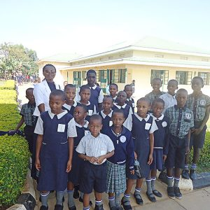 Sister Catherine Magoba, CSC, joins with a group of students at Moreau Nursery and Primary School in Kirinda, Uganda, who earned scholarships through the Ministry With the Poor Fund. (pre-pandemic photo)