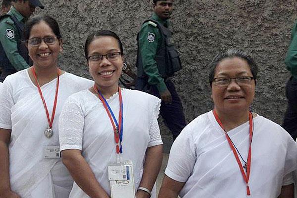 Sisters Kolpona Costa, Runu Mrong and Barnita Scholastica Mangsang stand waiting to enter Holy Rosary Church to meet with Pope Francis