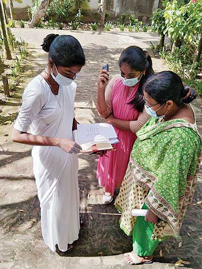Sister Repa Anna Costa, CSC, of Holy Cross High School in Bhadun, Bangladesh, reviews lesson plans with a student and her mother.