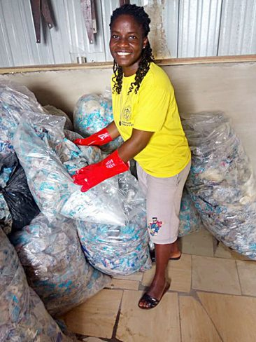 Sister Comfort Arthur, CSC, handles plastics collected for recycling, part of a multiprong initiative to address Ghana's plastic waste crisis, provide employment and educate the community.