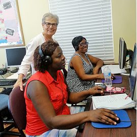 Sister Joan Carusillo, CSC, assists two clients from Haiti, Gurley Merise, left, and Marie Francigne, who are strengthening their computing skills during one of 30 weekly classes offered at the Women's Circle in Boynton Beach, Florida.