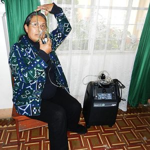 Sister Lilma Calsin Collazos, CSC, demonstrates the new oxygen concentrator machine used in her ministry to provide health care to prisoners in Lima, Peru.