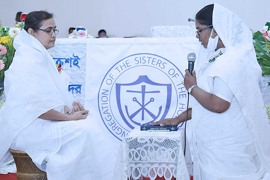 Area of Asia Coordinator, Sister Violet Rodrigues, CSC, left, receives Sister Teresa's vows during the perpetual profession Mass.