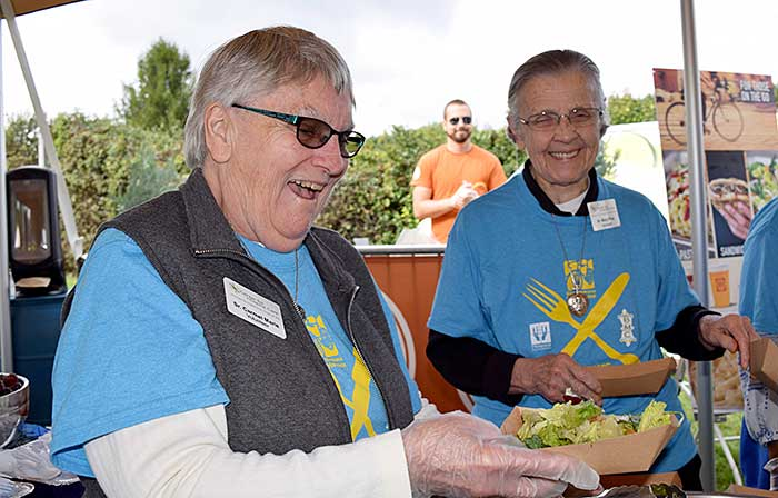 At the Bike Michiana fundraiser, Sister Carmel (left) serves up food with Sister Mary Pius (Schreiner).