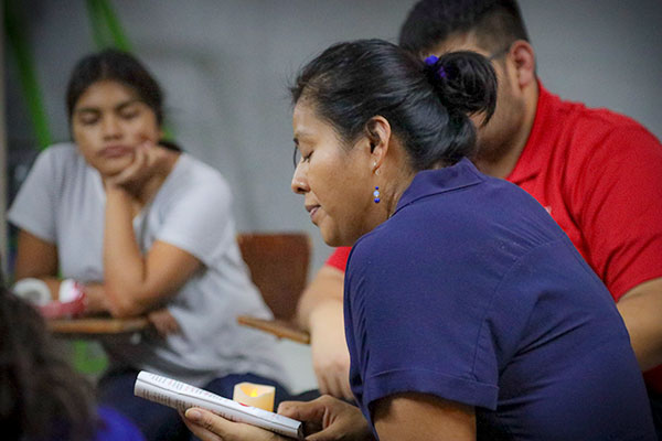 As part of her pastoral ministry, Sister Esperanza Jacobo Acevedo, CSC, reads the Gospel to migrants at Casanicolas in Guadalupe, Nuevo León, Mexico. Casanicolas provides migrants with shelter in a secure place, promotes human rights and offers pastoral care.   Photo credit Brother Nich Perez, CSC