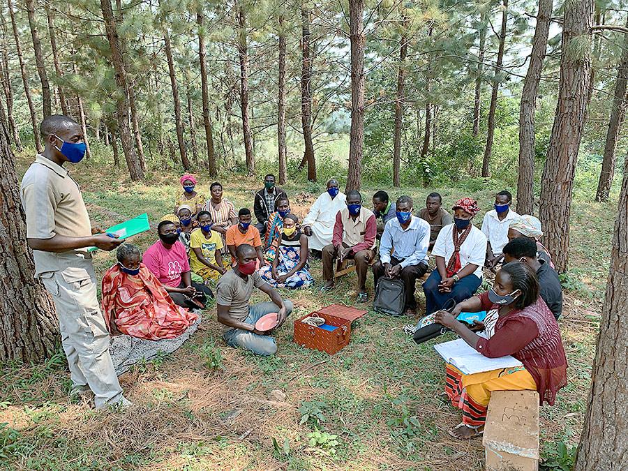 Members of the Kyamugenyi Kweterana group gather around their savings box to discuss their next steps.