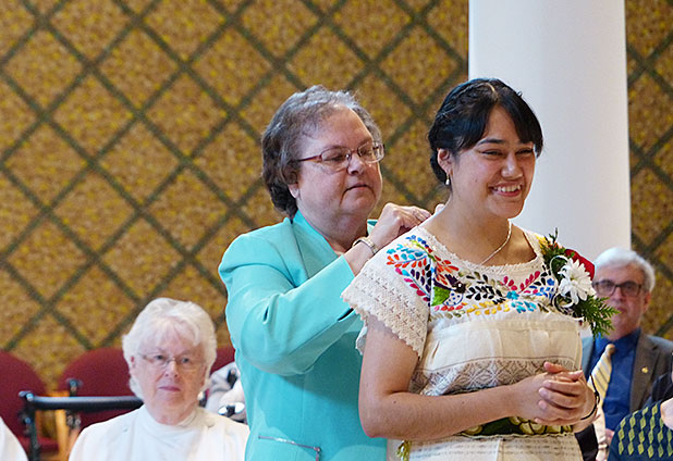Sister M. Veronique (Wiedower), CSC, gives Sister Nieves Lidia Ortiz Galván, CSC, the Holy Cross symbol as a sign of her commitment to living the vowed life in the Congregation of the Sisters of the Holy Cross.