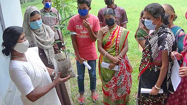 Following the parents' meeting at Holy Cross School, Kulaura, Bangladesh, Sister Shiuli (Gomes), CSC, (left) offers tree saplings as a sign of hope for a better future.