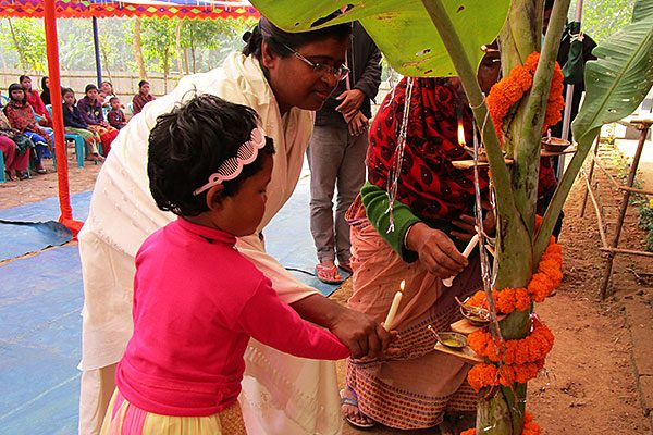 Sister Shiuli Gomes, CSC, helps a student light a candle during the opening ceremony.