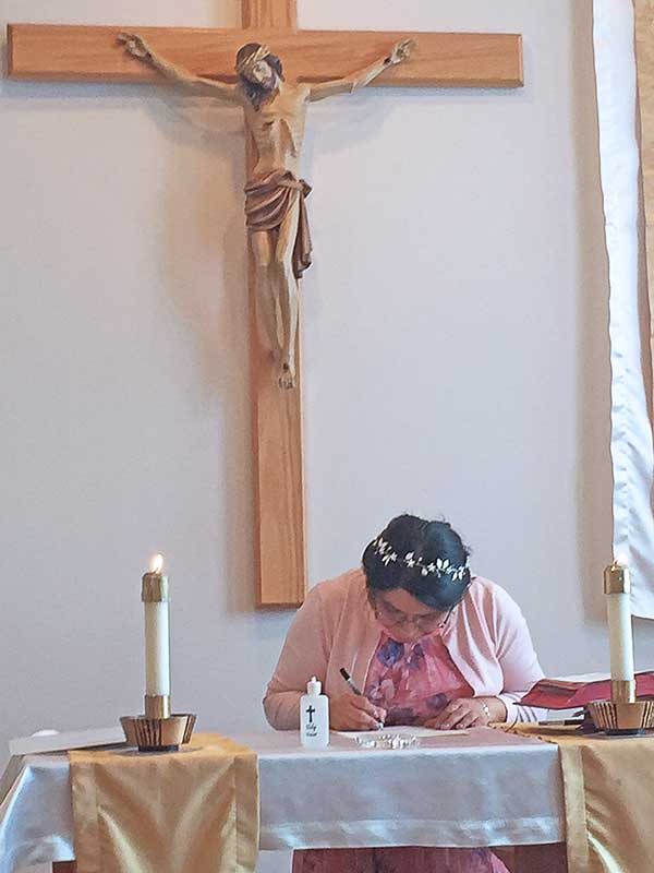 During the profession ceremony, Sister Laura Guadalupe Tiburcio Santos, CSC, signs her perpetual vows in the Congregation. In accepting the challenge of a vowed life in community, the sisters choose to follow Jesus' example and teachings in how they regard people, possessions and power.