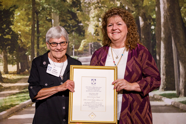 Photos provided by Saint Mary's College Pictured from left is Sister Carmel Marie (Sallows), CSC, receiving a framed citation from Saint Mary's College Interim President Nancy P. Nekvasil.