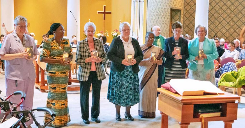 "Members of the newly installed 2019-2024 General Administration of the Sisters of the Holy Cross receive lit candles as a reminder of ""the light of the Spirit which guides our global desire for healing and wholeness."" From left, Sisters Catherine Osimo, Esther Adjoa Entsiwah, Kathleen Moroney, Mary Tiernan, Pushpa Teresa Gomes, Suzanne Brennan and M. Veronique (Wiedower)."