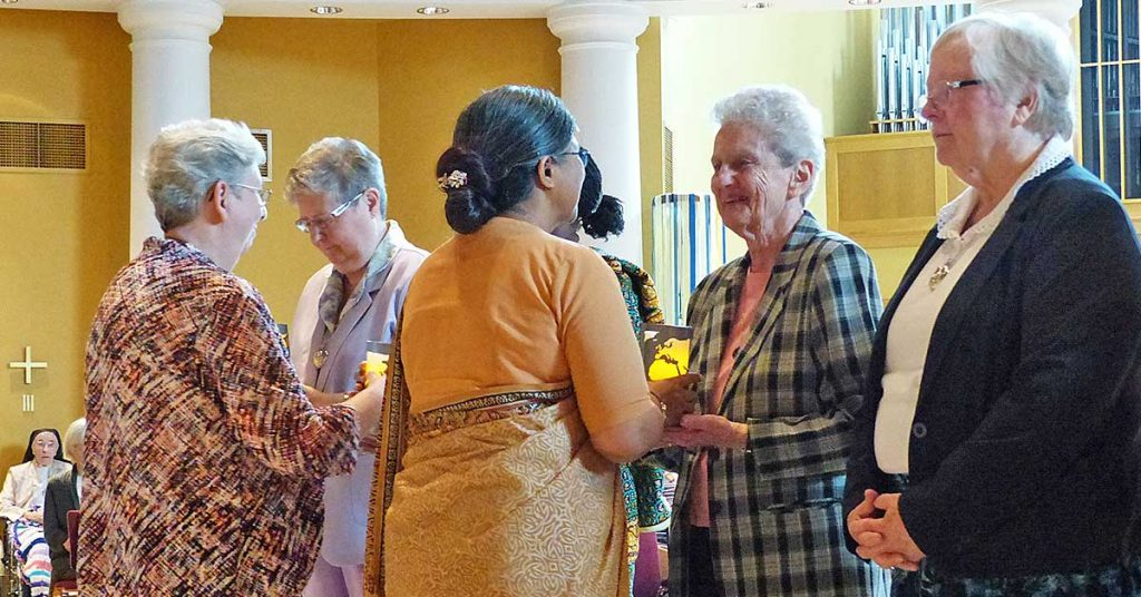 Holy Cross Sisters Brenda Cousins, left, and Angela Golapi Palma, members of the Congregation's 2014-2019 General Leadership Team, welcome incoming leadership members at the installation.