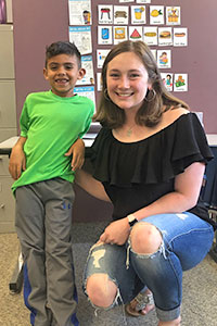 Annie Donohue, a Summer Service Learning Program student from the University of Notre Dame, is pictured with a young boy in the Holy Cross Ministries Summer Program.