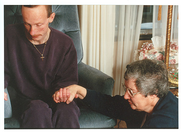 Sister Linda Bellemore of the Sisters of the Holy Cross comforting an HIV patient. Photo credit: unknown