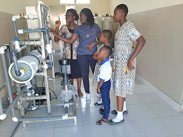 Sisters Bertha Akua Owusuaa, CSC, and Bernice Asare-Badu, CSC, share the new water filtration system with students at OLCHS