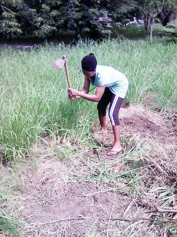 Sister Rita prepares the earth for planting.