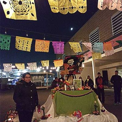 Sister Laura Guadalupe Tiburcio Santos, CSC, stands beside a beautifully decorated altar erected for a Day of the Dead/Healing Walk event she attended in Salt Lake City, Utah.