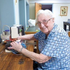 Busy at the sewing machine, Sister Mary Mulligan, CSC, helps turn out some protective masks for employees and sisters at the motherhouse.