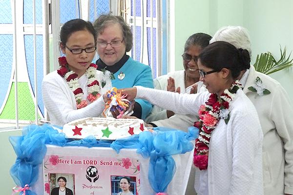 Sisters Khochem Mossang and Bijoycy Thongnibah cuting the cake served at the reception.