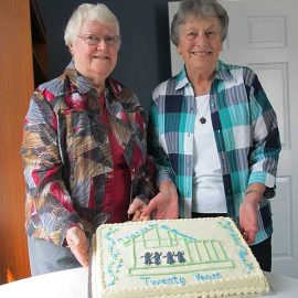 Sisters Mary Margaret Weber, CSC, and Judith Hallock, CSC, stand with the beautiful cake made especially for the farewell celebration.