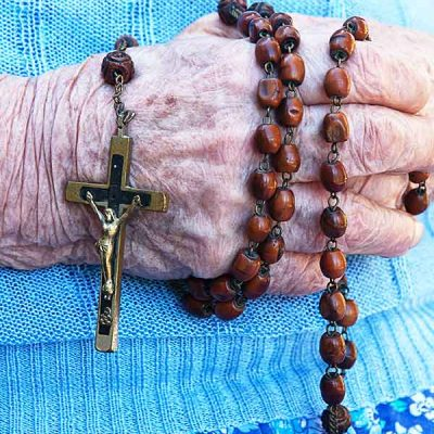 hand holding a rosary, Fruits of Holy Cross, ministry of prayer