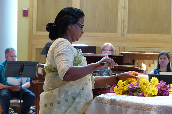 Honoring diamond jubilarians who have gone to God, silver jubilarian Sister Shilpi Rozario, CSC, lights the candle of remembrance during the jubilee Mass.