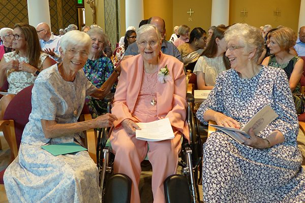 Diamond jubilarian Sister M. Carmen (Davy), CSC, honored for her 75 years of religious life, enjoys the company of Sister Frances B. O'Connor, CSC, left, and family members during jubilee.