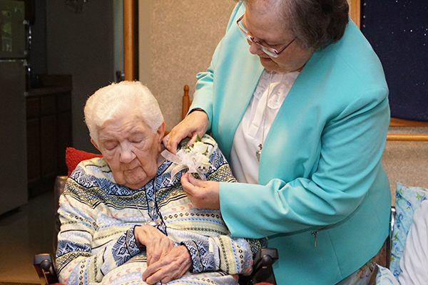 Diamond jubilarian Sister M. St. Brigid (Bromeling), CSC, honored for her 75 years of religious life, receives a flower corsage from Sister M. Veronique (Wiedower), Congregation president, during the jubilee events.