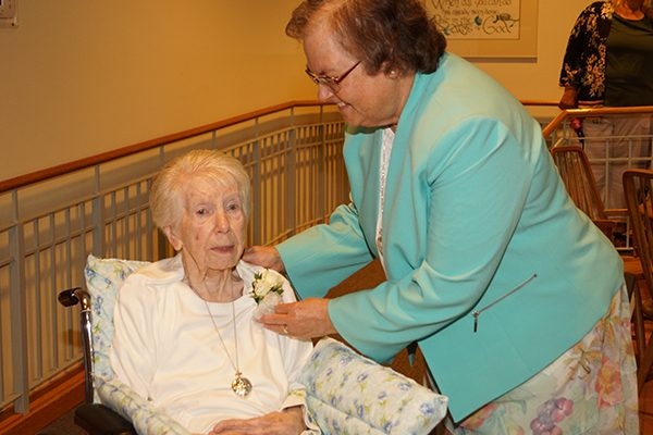 Diamond jubilarian Sister M. Georgia (Costin), CSC, honored for her 75 years of religious life, receives a flower corsage from Sister M. Veronique (Wiedower), Congregation president, during the jubilee events.
